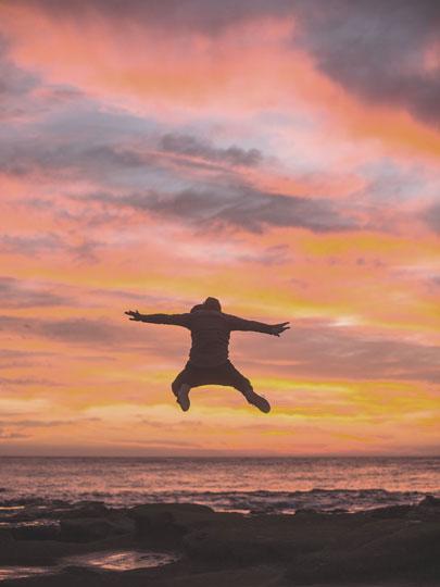 Personne sautant sur une plage au coucher du soleil